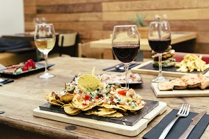 Traditional atmosphere with plate of nachos and glass of red wine