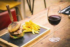 Traditional chips and burger with glass of red wine