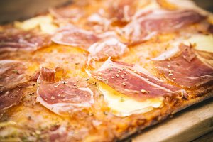 Detail of rustic ham and brie cheese pizza
