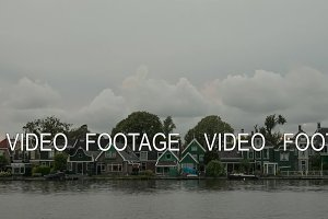 Timelapse of clouds over houses on river bank, Netherlands