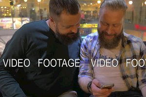 Close up view of two white mature bearded men using smartphone together