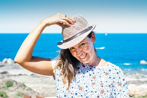 Smiling woman holding hat at seaside