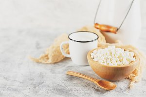 Granulated cottage cheese in wooden bowl and mug of milk