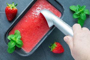 Woman scooping strawberry sorbet out of tray, top view