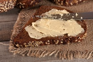 slice of black bread with sesame seeds and butter on the old wooden background