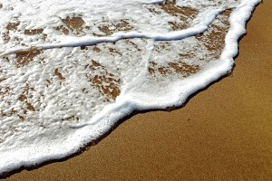foamy wave of the sea splashing on a sandy beach