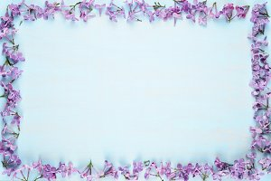 Frame of lilac flowers on blue wood