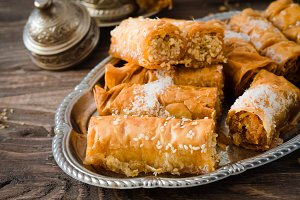 Homemade baklava rolls in iron try on wooden background. Ramadan food. Selective focus