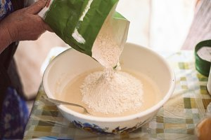 Pouring flour into pancake batter