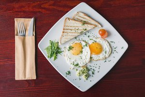 Breakfast in restaurant - fried eggs on white plate with green and tomato cherry