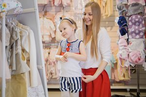 Shopping for kids - cute little girl with mommy buying outfit in store of kids clothes