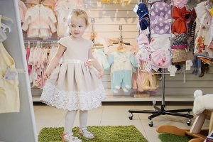 Blonde little girl chooses new dress near mirror in store of kids clothes