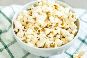 bowl of salty popcorn and soda