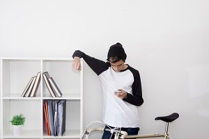 young man with the phone at home and vintage bicycle, technology and lifestyle