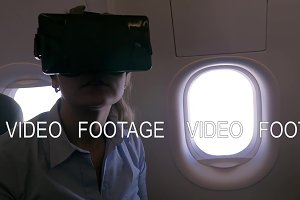 Slow motion view of woman using VR-helmet for smartphone in airplane