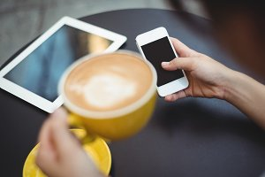 Woman using mobile phone while having coffee