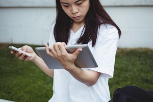 Young woman using mobile phone and digital tablet