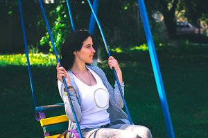 Young beautiful girl on a swing in the park emotions concept.