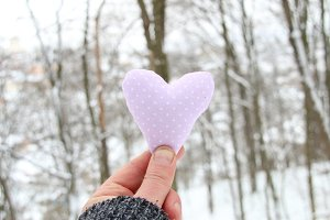 Winter, Love or Valentine's Day idea. Hand holding a heart on the background of the winter forest