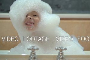 Happy child in foam taking bath