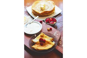 Closeup of homemade pancakes with fruits on black transparent dish on wooden table. Raspberry, strawberry and sour cream ingridients on wooden background.