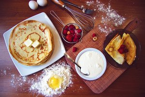 Top closeup view of homemade pancakes with fruits on dishes. Strawberry, raspberry, eggs in flour and sour cream ingridients on wooden background.
