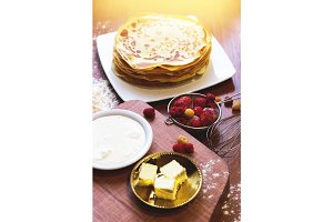 Closeup of homemade pancakes, butter and sour cream on dishes with strawberry and raspberry on wooden background.