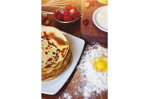 Closeup of pancakes on dishes. Strawberry, raspberry, eggs in flour and sour cream ingridients on wooden background.