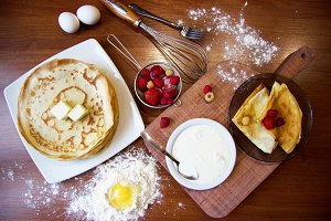Top closeup view of pancakes with fruits, sour cream and butter on dishes. Strawberry, raspberry and eggs in flour ingridients on wooden background.