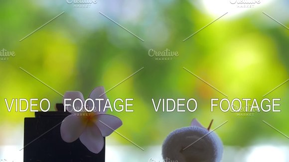 Slow motion view of falling petals of flowers against green blurred background on the table with flower Plumeria and towels