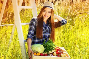 Pretty and young smiling girl in hat keeping wooden box full of vegetables. Summer harvest.