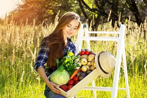 Pretty and young smiling girl keeping wooden box full of vegetables. Summer harvest.