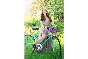 Young beautiful girl with long hair in bright dress with flowers in basket on vintage bike. Fashioned woman.