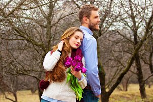 Romantic love story. Portrait of beautiful young couple in casual clothes back to back together with flowers on the garden.