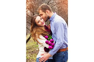 Happy couple together. Portrait of bearded man kissing his lovely girlfriend with flowers on the garden.