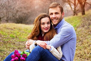 Happiness is close to you. Portrait of happy beautiful young couple sitting together and smiling on the garden.