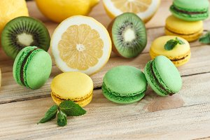 Green and yellow macarons with kiwi, lemon and mint decorations