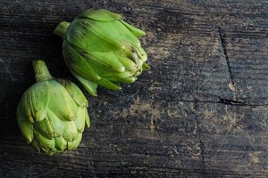 Two artichokes on rustic table