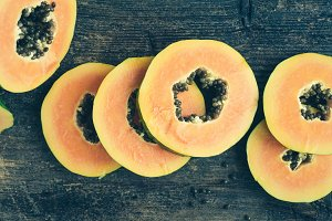 Slices of sweet papaya on wooden background