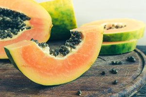 Slice of sweet papaya on wooden background
