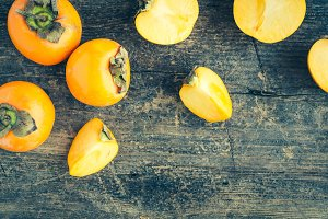 Delicious fresh persimmon fruit on wooden table