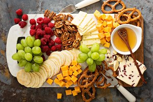 Cheese and snacks platter with honey and fresh fruit