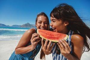 Young women enjoying watermelon