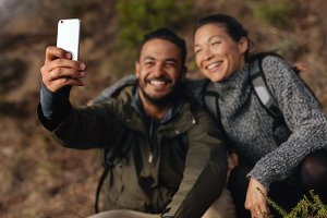 Young couple hiking taking selfie