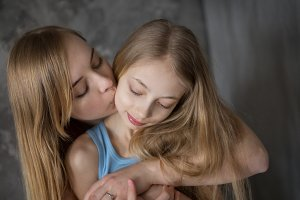 Mom and daughter teenager embrace