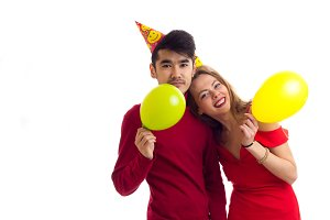 Young couple blowing balloons