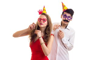 Young couple with card sticks and celebrating hats