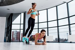 Young fit female athletes working-out in pair, girl jumping over her friend while woman performing plank position.