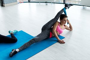 Young woman doing side lying leg split exercise with resistance band on mat during stretching class in fitness club