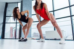 Sexy young women wearing leotards and trainers dancing modern standing in tempting positions indoors
